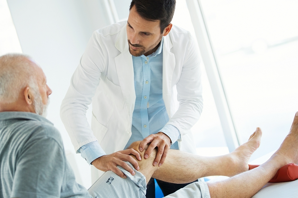 Man with knee pain is being examined by a physiotherapist.